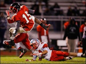 Bowsher's  Kolton Davis (4) trips up Rogers player Wendell Warren (15).
