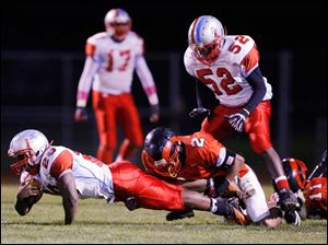 Rogers' Kameron Jones (2) tackles Bowsher High School player Khane Collins (20) during the first quarter.