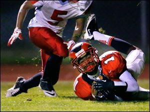 Rogers' Anthony Amison (11) makes the catch for a touchdown against Bowsher High School player Derrick Chandler (5).