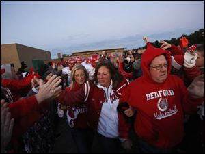 Mary, center, and Mark Durbin, right, lead the football team down a tunnel created by students and community members as they take the field before the start of the game.