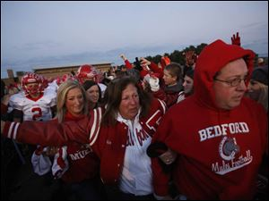 Mary, center, and Mark Durbin, right, lead the football team down a tunnel created by students and community members.