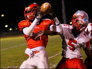 Rogers player Anthony Amison (11) catches a pass against Bowsher's Derrick Chandler (5).