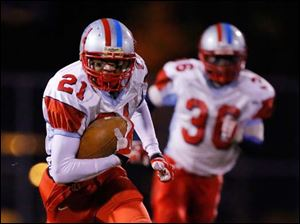 Bowsher's Ka'Ronn Osley (21) runs back an interception against Rogers High School during the second quarter.