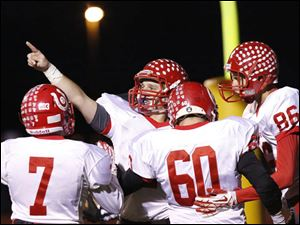 Bedford senior quarterback Brad Boss (2) center, raised his hands up after scoring the first touchdown of the game.