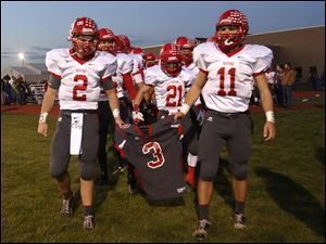 Bedford senior quarterback Brad Boss (2) and senior Alec Hullibarger (11) carry the jersey of their teammate Colton Durbin as they lead their team onto field before the start of the game.