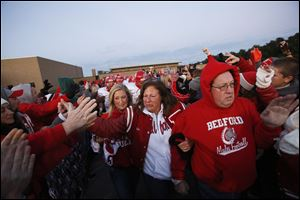 Mary, center, and Mark Durbin, right, lead the football team down a tunnel created by students and community members as they take the field before the start of Bedford's game against Monroe Jefferson on Friday.