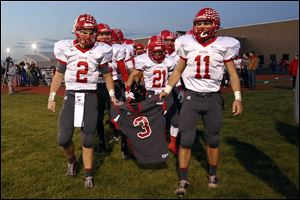 Bedford senior quarterback Brad Boss (2) and senior Alec Hullibarger (11) carry the jersey of their teammate Colton Durbin as they lead their team onto the field at Jefferson High School in Monroe.