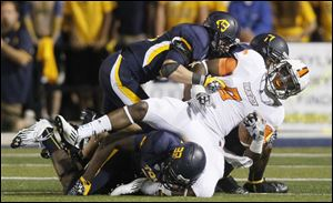 Bowling Green receiver Shaun Joplin is brought down by Toledo defenders Sylvestre, 33, Mark Singer, 43, and Cheatham Norrils, 11, during the football game at the Glass Bowl in 2012.