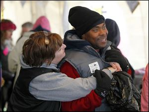 Betsy Byersmith, chairman of the clothing tent, hugs volunteer Terrance Burch.