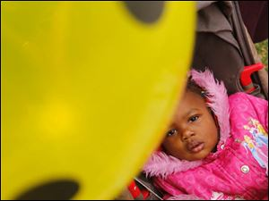 Yealaysia Williams, 18 months-old, stares at her balloon as she waits to go inside the clothing tent.
