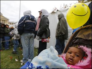 Yealaysia Williams, 18 months-old, waits to go inside the clothing tent with her mother Deborah Williams, Toledo.