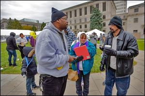 Ray Mays of Toledo, left, speaks with Jennifer Pritchard and her fiancee John Proeschel as the pair wait for clothing at Tent City on Toledo's Civic Center Mall. Mr. Mays is the mayor of Tent City.