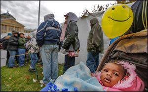 Yealaysia Williams, 18 months old, waits outside the clothing tent with her mother, Deborah Williams of Toledo, at Tent City  on the Civic Center Mall. A bullet fragment is lodged in the child's back and her mother says she wants to move to a low-income apartment in a safer