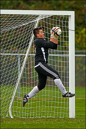 St. John's goalkeeper Stephen Wainz cradles a Perrysburg shot during the District I final.