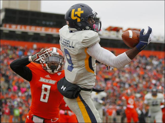 University of Toledo player Alonzo Russell (9) makes a one-handed catch for a touchdown over Bowling Green State University player Cameron Truss (8) during the second quarter.