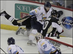 Walleye C.J. Chartrain (3) collides with two Nailers defenders in pursuit of the puck during the second period.