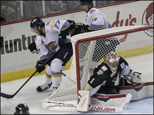 Walleye Trevor Parks (27) swings around the net during the second period.