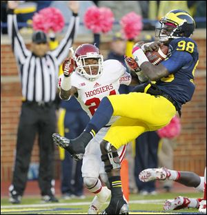 Michigan quarterback Devin Gardner takes a big hit from Indiana's Tim Bennett after scoring a touchdown during their Oct. 19 game in Ann Arbor. Bennett was flagged for a personal foul on the play.