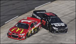 Sprint Cup Series driver Jamie McMurray, left, and Kurt Busch spin out during the NASCAR Sprint Cup  race in Martinsville, Va.