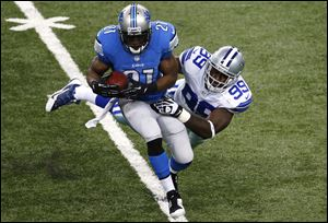 Lions running back Reggie Bush is brought down by Dallas Cowboys defensive end George Selvie in the first half Sunday in Detroit.