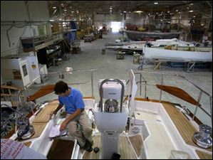 Anthony Crimmins, a process engineer, checks over a 47-foot-long yacht in production at Hanover Marine in Fairport Harbor.