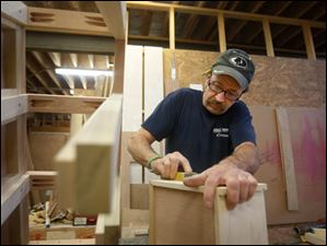 Cabinet maker Jim Gersin, a 20 year employee, crafts a cherry cabinet for a custom yacht.
