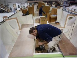 Patrick Kordos, center, works on assembling one of the custom yachts in production at Hanover Marine in Fairport Harbor.