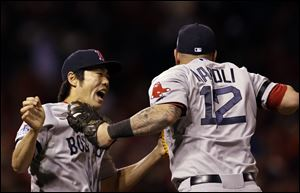 Boston's Koji Uehara and Mike Napoli celebrate after the Red Sox beat the Cardinals 4-2 in Game 4 of World Series on Sunday in St. Louis. The Red Sox tied the series at 2-2.