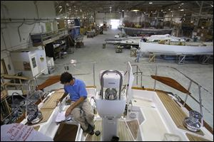 Anthony Crimmins, a process engineer, checks over a 47-foot-long yacht in production at Hanover Marine in Fairport Harbor. The business, located just outside Cleveland, is struggling to repay a loan from the state.