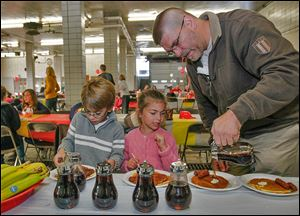 Garrett Hill, 7, left, his sister Marcie, 5, and their dad, firefighter Glenn Hill, dig into their pancakes. The event was set up to aid the family of former battalion Chief Peter J. Jaegly, who died Oct. 6.