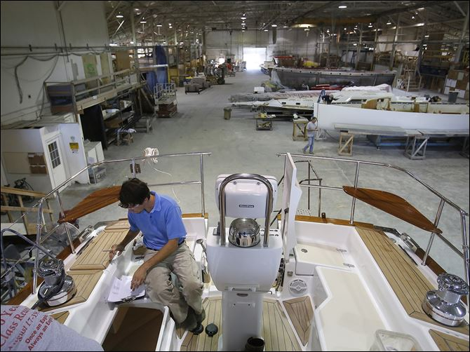 29n3yacht-1 Anthony Crimmins, a process engineer, checks over a 47-foot-long yacht in production at Hanover Marine in Fairport Harbor. The business, located just outside Cleveland, is struggling to repay a loan from the state.