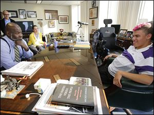Dallas King, 18, right, sits in Mayor Mike Bell's chair Tuesday at One Government Center in Toledo. The Whitmer High senior, who has cerebral palsy, recently made a a PowerPoint presentation for his classmates about his skydiving adventure.