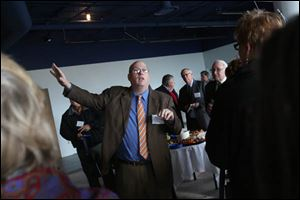 Chris Gillcrist executive director of the Great Lakes Historical Society, directs the group of more than 50 people who had come to tour the partially renovated National Museum of the Great Lakes near downtown Toledo.