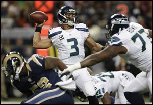 Seattle Seahawks quarterback Russell Wilson (3) works against the St. Louis Rams during the first half.