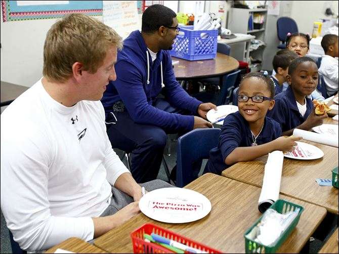 CTY visit29p Heaven Golladay, 8, smiles while eating pizza and talking with Toledo Rockets sophomore Derek Batt.