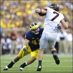 Michigan's Desmond Morgan tackles Minnesota quarterback Mitch Leidner. Morgan has 47 tackles.