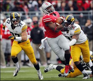 Ohio State's Carlos Hyde gets past Iowa's Anthony Hitchens, right. Hyde has 590 yards on 88 carries with seven touchdowns this year.