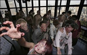 Participants wearing zombie makeups perform during a Halloween event at Tokyo Tower.
