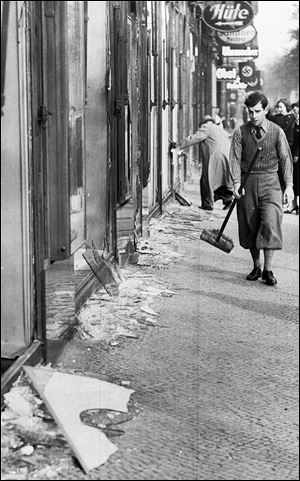 A young man with a broom prepares to clean away broken window glass from a Jewish shop in Berlin the day after Kristallnacht, Nov. 9, 1938.