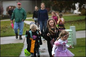Katelyn Feltz, 6, left, peeks in her bag as she and Chloe Erickson, center, join trick-or-treaters in Bed-ford Township. Unlike several area communities, Bedford did not cancel trick-or-treat Thursday.