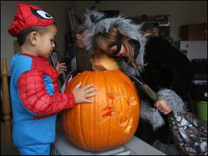 David Clare, 3, left, and his sister Harmony, 5,peer inside a pumpkin as they wait out of the rain.