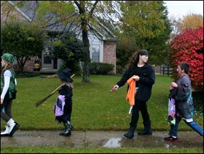 Paige Kamer, 10, left, Kylie Pakulski, 6, center left, Payton Kamer, 12, center right, and Mitchell Pakulski, 9, all of West Toledo, raced from house to house while trick-or-treating in Bedford on Halloween. Many cities, including Toledo, moved their trick-or-treating to Sunday in hopes of avoiding the rain.