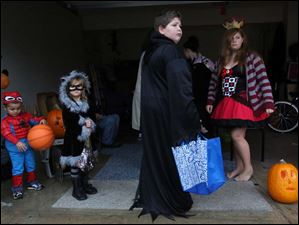 David Clare, 3, left, Harmony Clare, 5, center left, David Stevenson, 11, center right, and Vanessa Stevenson, 13, right, wait out of the rain for the start of trick-or-treating in Bedford on Halloween.