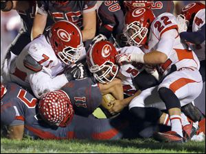 Bedford High School player Alec Hullibarger (11) is tackled by Westland John Glenn High School players Renardo Brown (71) Jordan Brandon (55) and Leon Crawford (22) during the second quarter.