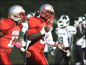 Bowsher's Mark Washington, center, cheers after scoring a  break away touchdown.