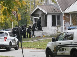 Toledo Police department personnel enter the house at 1105 Montrose.  A suspect in a shooting and robbery attempt was removed from his house Toledo officers.