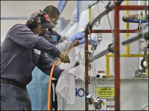 Employees at Sheffield Platers Inc. work on the factory floor in San Diego.