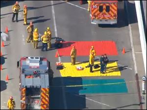 In this aerial video frame grab provided by CBS-LA, fire and rescue personnel gather at Los Angeles International Airport.