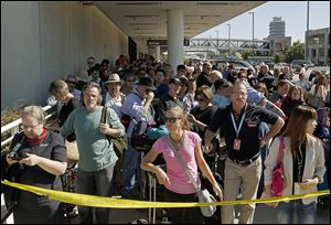 Evacuated passengers wait outside Los Angeles International Airport, where flights were halted.