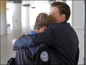 Transportation Security Administration employees grieve at Los Angeles International Airport. A gunman opened fire on Friday, killing a TSA worker. A number of other people were hurt in the pandemonium.